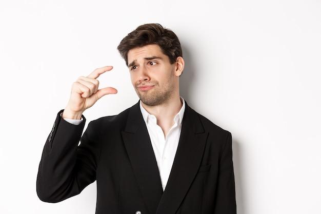 トレンディなスーツを着たハンサムなビジネスマンのクローズアップ、失望と小さな何かを示し、白い背景に立って