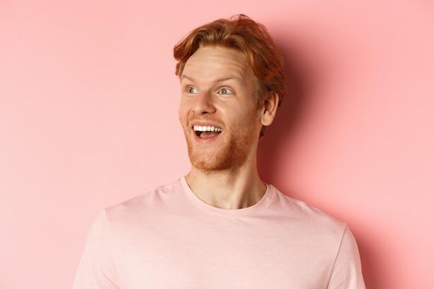 Крупный план красивого кавказского парня с рыжими волосами и бородой, смотрящего влево со счастливой улыбкой, проверяющего промо-предложение, стоящего на розовом фоне