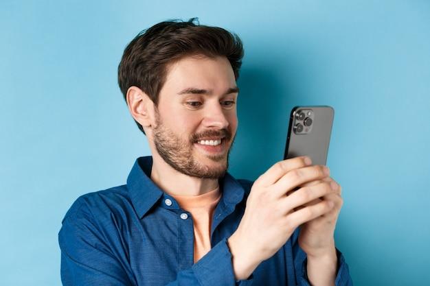 メッセージを書いている、モバイル画面を読んで、笑顔、青い背景の上に立っているハンサムな白人男性のクローズアップ。