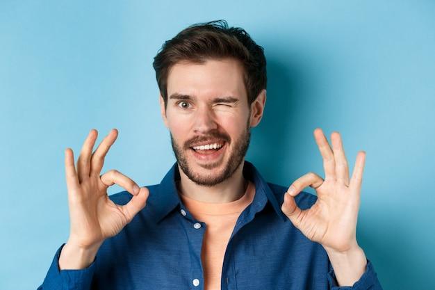 Крупным планом красивый уверенный в себе парень, подмигивающий, показывающий хорошие жесты, гарантирующий качество, рекомендующий что-то хорошее, стоящий на синем фоне.