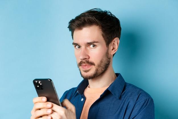 스마트 폰을 사용 하 고 파란색 배경에 서있는 카메라를보고 잘 생긴 유럽 남자의 클로즈업.