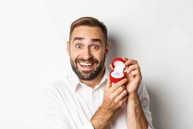 提案をし、希望を持って結婚指輪を見せ、彼と結婚するように頼むハンサムな男のクローズアップ、白い背景。
