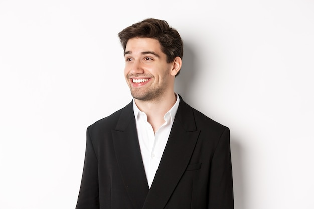 Крупным планом красивый мужчина-предприниматель в костюме, глядя влево и улыбаясь, стоя на белом фоне.