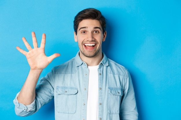 青い背景の上に立って、5番目の指を示して笑っているハンサムな男のクローズアップ。