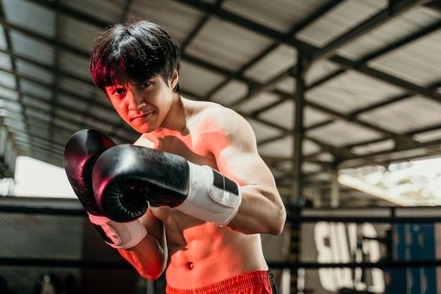 Copyspace와 권투 링에서 장갑에서 싸우는 잘 생긴 무에타이 권투 선수의 닫습니다