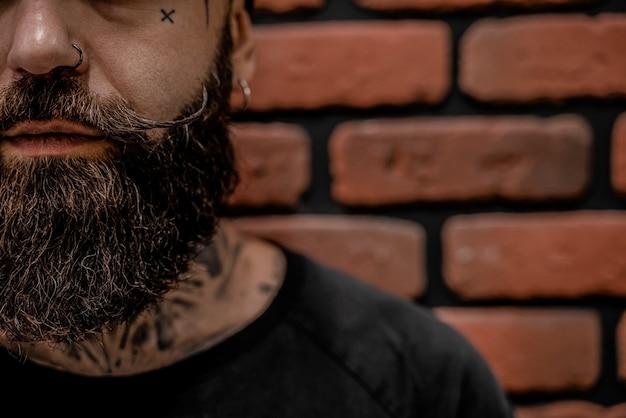 문신 및 벽돌 배경에 피어싱 잘 생긴 구식 hipster의 클로즈업.