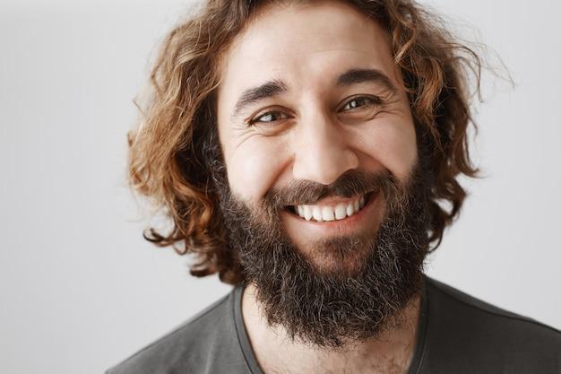 幸せなハンサムな笑みを浮かべてひげを生やした中東男のクローズアップ