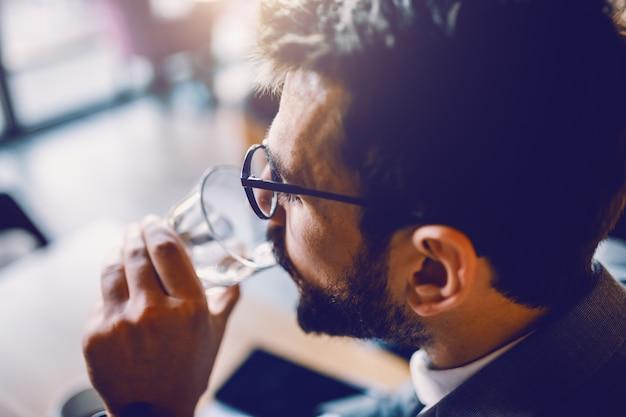 カフェに座っていると新鮮な水を飲む眼鏡とスーツのハンサムなのどが渇いて白人ひげを生やした実業家のクローズアップ。