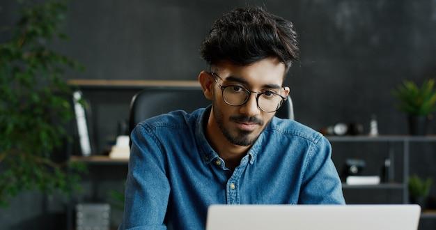 テーブルに座っているとラップトップコンピューターで作業してハンサムな若いアラブ忙しい男性会社員のクローズアップ。