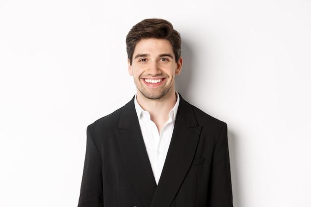 Крупным планом красивый молодой бизнесмен в модном костюме улыбается, стоя на белом фоне