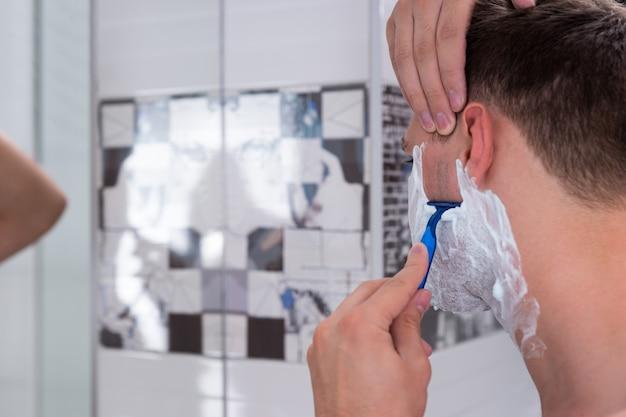 집에 있는 현대적인 타일 욕실에서 면도기로 면도하는 잘생긴 청년의 클로즈업