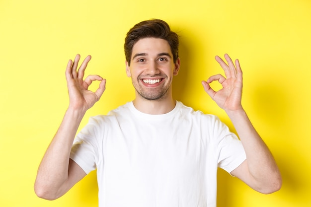 大丈夫な兆候を示し、承認して同意し、満足して笑って、黄色の背景の上に立っているハンサムな若い男のクローズアップ。