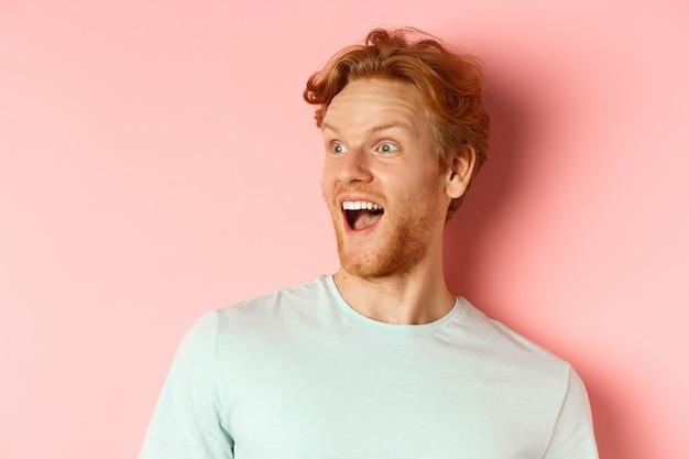 Крупный план счастливого и очарованного молодого человека с рыжими волосами, проверяющего промо-сделку, смотрящего влево с изумленной улыбкой, стоящего на розовом фоне