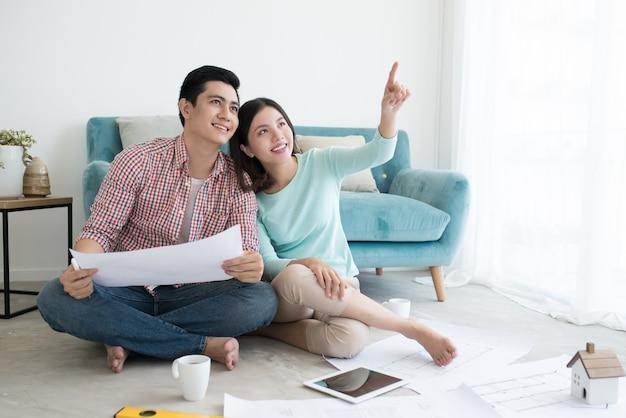 家で青写真を見ている幸せなアジアのカップルのクローズアップ