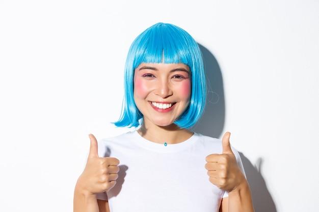 Крупный план счастливой азиатской девушки в голубом парике, улыбающейся и одобрительно показывающей большие пальцы руки