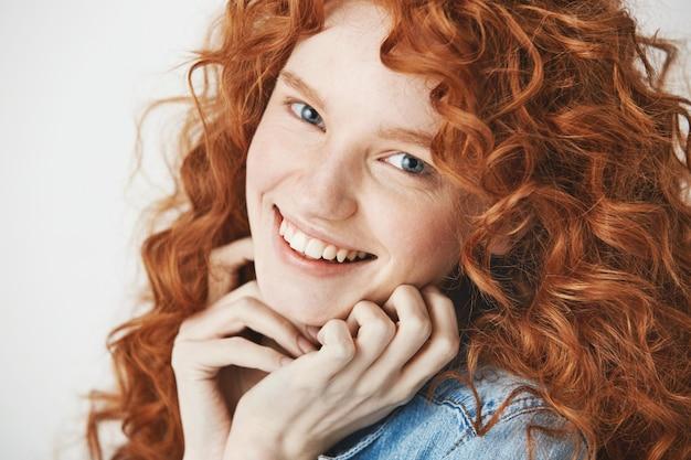 Крупным планом счастливой красивой девушки с вьющимися волосами имбирь улыбается