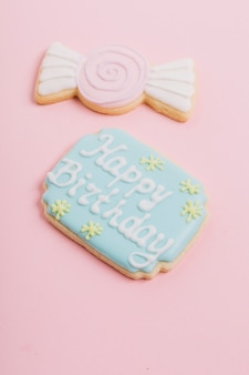 Close-up of happy birthday text on cookie over pink background