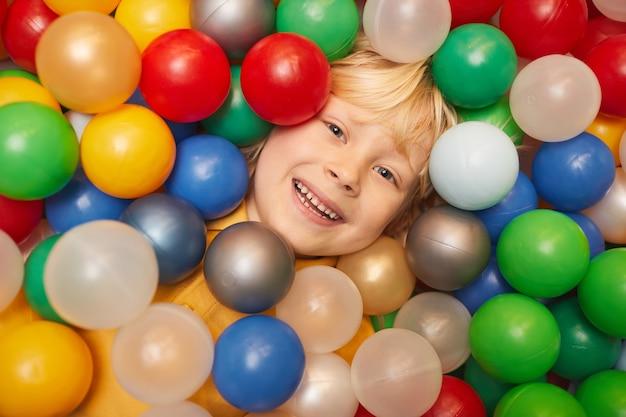 Крупный план счастливого мальчика со светлыми волосами, улыбающегося спереди, лежа среди цветных шаров и играя