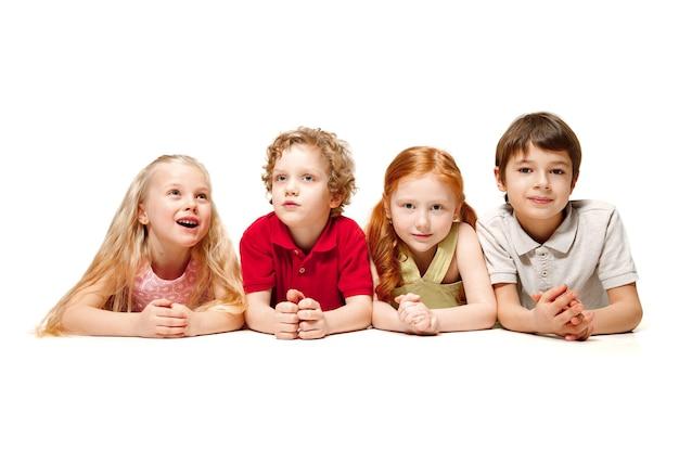 흰색 배경에 격리된 채 스튜디오 바닥에 누워 올려다보는 행복한 아이들의 클로즈업. 아이 감정, 책의 날, 교육, 학교, 아이, 지식, 어린 시절, 우정, 연구 개념