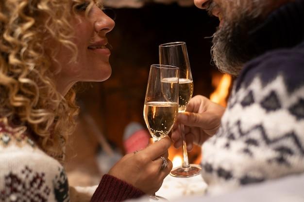 バックグラウンドで暖炉のあるワインのフルートをチリンと愛する幸せなカップルのクローズアップ。冬の休暇中に家で関係を楽しんでいるロマンチックな人々。一緒に男性と女性の概念