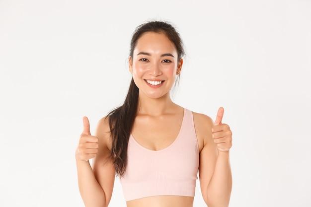 幸せなかわいいブルネットのアジアの女の子のクローズアップ、満足そうに見えるフィットネスインストラクター、親指を立てて笑顔を見せて、良いトレーニングを賞賛します。