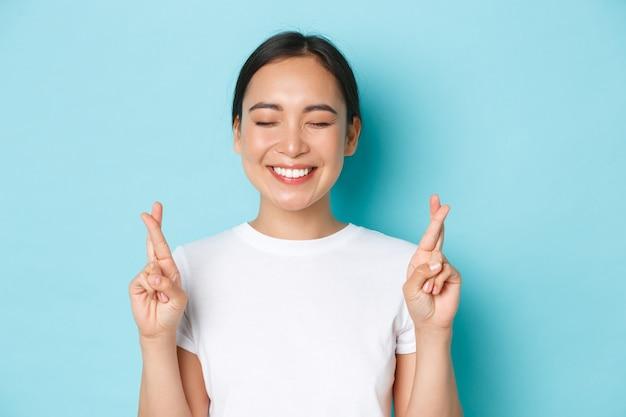 행복 꿈꾸는 젊은 아시아 여자의 근접 소원, 눈을 감고 행운을 빌어 손가락을 교차, 공상, 좋은 것을 기대하고, 뉴스를 기대하고, 하늘색 벽에 서서