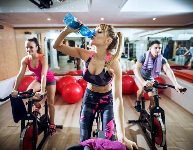 Закройте вверх счастливых сфокусированных профессиональных молодых людей ехать фитнес велосипед в спортзале пока девушка в разбивочной питьевой воде.