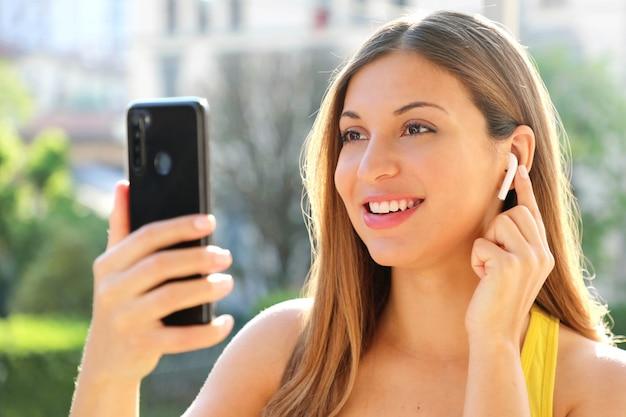 夏の晴れた日に屋外のワイヤレスイヤホンで彼女のスマートフォンで音楽を選択する幸せな女の子のクローズアップ