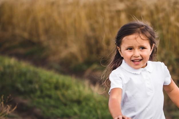 보 리 필드를 통해 카메라를 실행하는 긴 금발 머리를 가진 행복 한 여자의 닫습니다. 밀 초원 위에 조깅 작은 웃는 아이. 황금 농장에서 시간을 보내는 귀여운 아이. 느린
