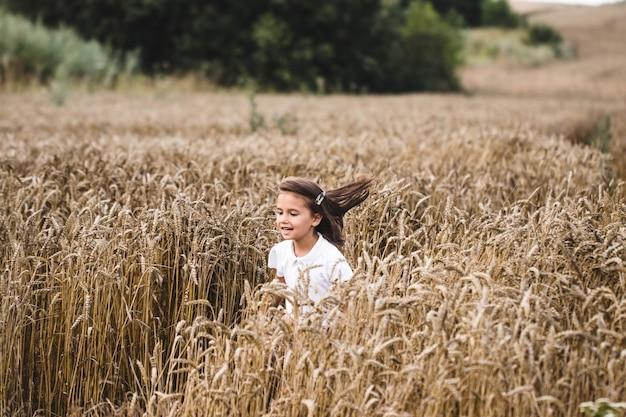Закройте вверх счастливой девушки с длинными светлыми волосами, бегущими к камере через поле ячменя. маленький улыбающийся ребенок, бег над пшеничным лугом. милый ребенок, проводящий время на золотой плантации. замедленная съемка