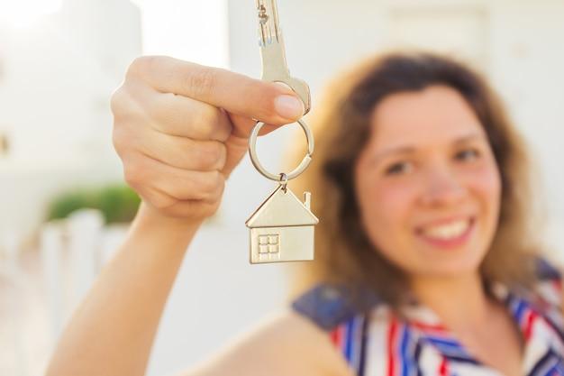 열쇠를 보여주고 당신을 바라보는 행복한 집주인이나 세입자의 클로즈업