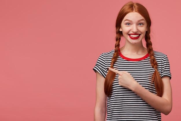 幸せなインスピレーションを得た赤い髪の十代の少女のクローズアップは、左側の空きスペースに人差し指で表示され、製品に満足しており、注意を払うことをお勧めします、あなたの広告のための場所