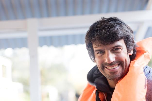 オレンジライフジャケットとの幸せな男のクローズアップ