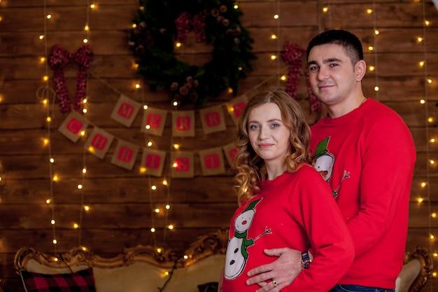 Закройте счастливую супружескую пару, связывающуюся рядом с елкой лучший рождественский подарок