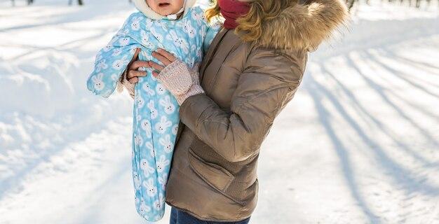 Крупным планом счастливая мать и ребенок в зимнем парке