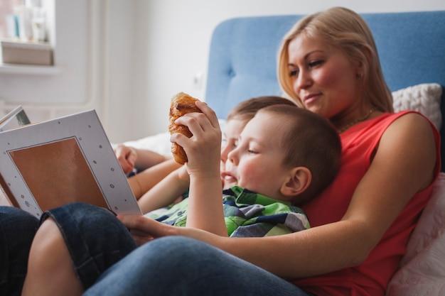 彼女の子供たちに本を読んでいる幸せな母親のクローズアップ