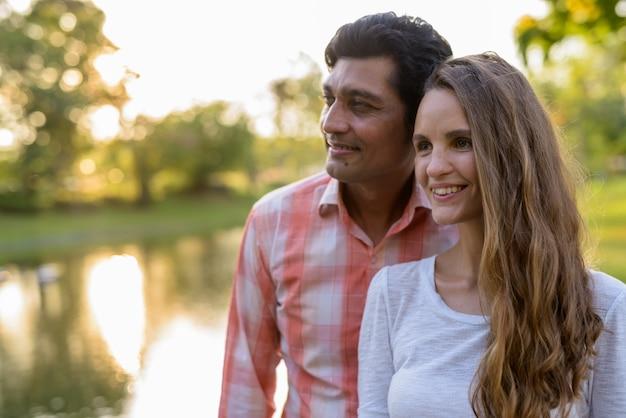 笑顔と考えて幸せな多民族のカップルのクローズアップ