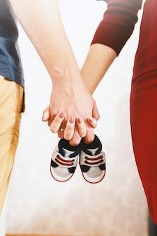 赤ちゃんを待っていると手を繋いでいる幸せな親のクローズアップ。手にベビーシューズ。