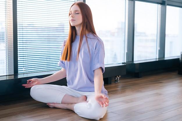 明るいオフィスルームの窓の背景に蓮のポーズで床に座って瞑想幸せな平和な若い女性のクローズアップ。
