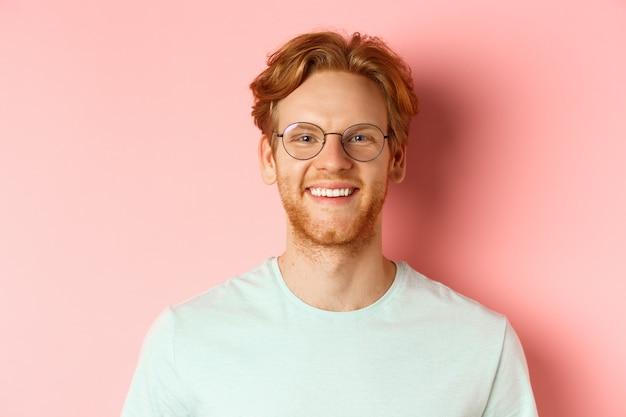 幸せな赤毛の男の顔のクローズアップ、カメラで白い歯で笑って、より良い視力とtシャツのために眼鏡をかけて、ピンクの背景の上に立っています。