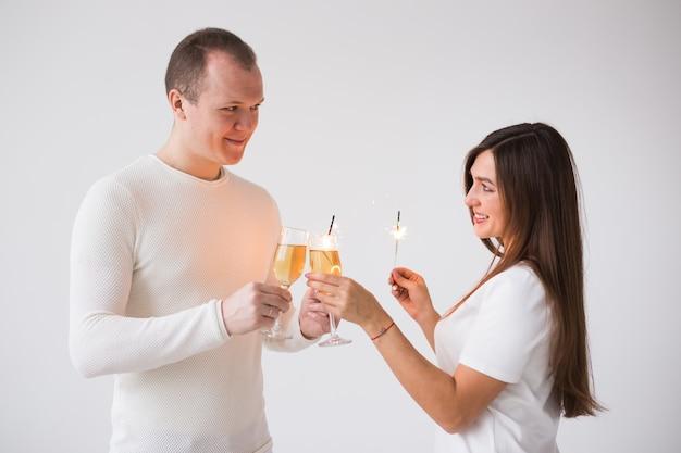 샴페인으로 축하하고 폭죽을 들고 행복 웃는 쾌활한 매력적인 커플의 닫습니다