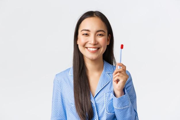 朝に歯ブラシで歯を磨いた後、白い背景に立っている新しい歯磨き粉の味に満足して立っている白い歯を示す幸せな笑顔の女の子のクローズアップ。