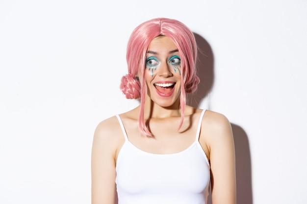 ピンクのかつらで幸せな驚きの女の子のクローズアップ、驚いた左を見て、笑顔、白い背景の上に立って