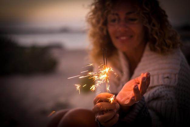 線香花火の光を保持し、屋外を祝う幸せな女性のクローズアップ