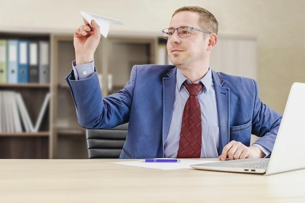 Крупным планом счастливый молодой кавказский бизнесмен весело бросить бумажный самолетик на рабочем месте, улыбаясь, мужчина-босс или работодатель занимается творческой деятельностью, думая в офисе