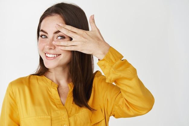 Крупный план счастливой молодой женщины, смотрящей сквозь пальцы и улыбающейся, стоящей над белой стеной