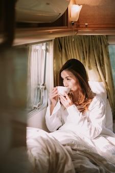ベッドでコーヒーやココアの飲み物と幸せな若い女性のクローズアップ