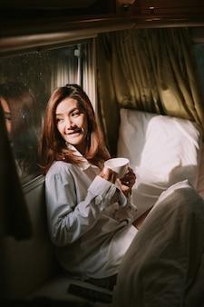 침대에서 커피나 코코아 음료를 마시는 행복한 젊은 여성 클로즈업