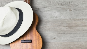 Close-up of hat over the guitar against wooden background