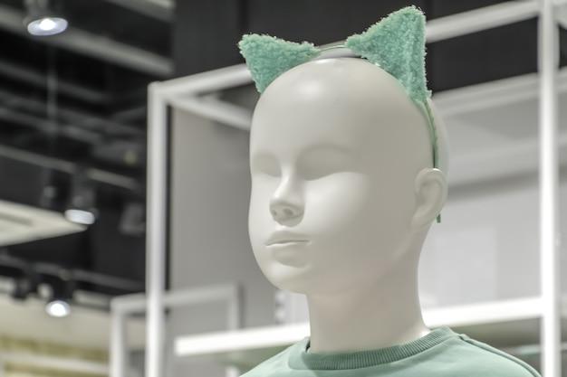 ミントの耳が付いたヘッドバンドを身に着けている白いプラスチックの赤ちゃんマネキンの頭のクローズアップ。子供服店、カーニバルコスチューム、コスプレ。子供のファッション業界。